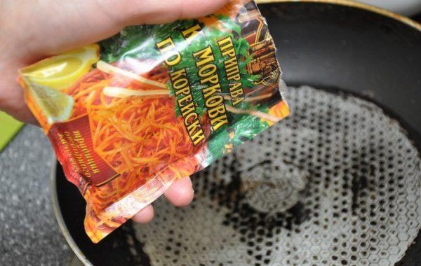 Большая скорода и пакетик с приправой для моркови по-корейски в руке человека