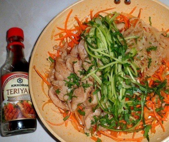 Заготовка для хе из курицы по-корейски с овощами в большой миске и бутылочка соуса терияки