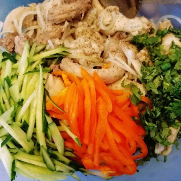 Кусочки отварной курицы с нарезанными свежими овощами и рубленой зеленью в миске