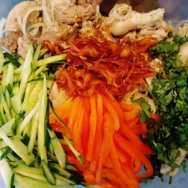 Кусочки варёной курицы, свежие овощи и обжаренный со специями лук в миске