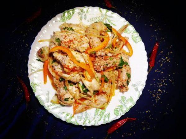 Хе с куриными шейками, крылышками и овощами на белой тарелке