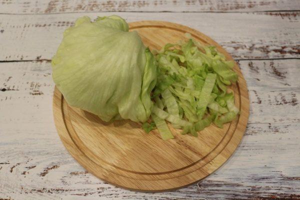 Кочан айсберга и нарезанный салат на круглой разделочной доске из дерева