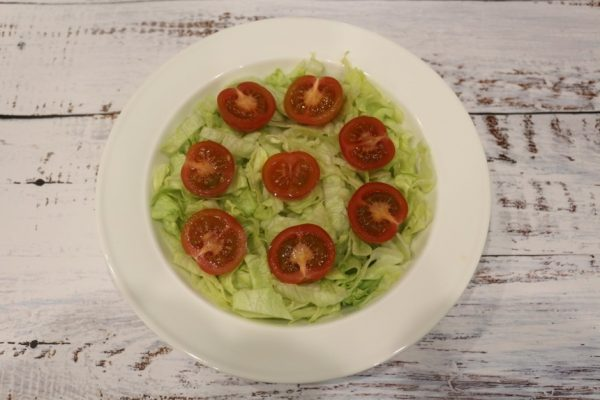 Нарезанный соломкой салат айсберг и половинки черри на большой тарелке белого цвета
