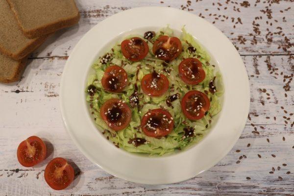 Салат из айсберга и черри с семенами кунжута и льна на большой белой тарелке
