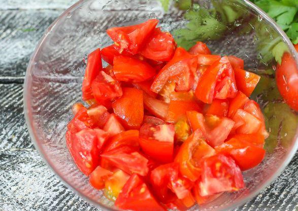 Нарезанные кусочками спелые помидоры в стеклянной миске на столе