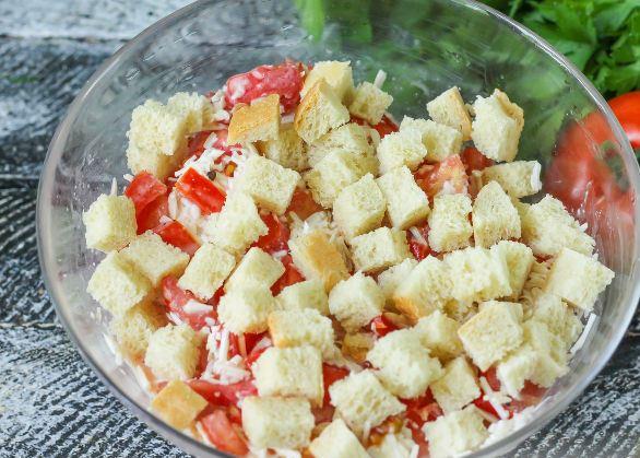 Салат с помидорами, плавленым сыром и сухариками в стеклянной миске на столе