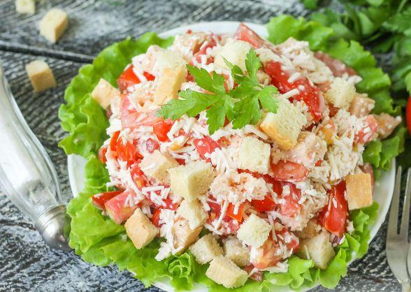 Салат с помидорами, плавленым сыром и сухариками на большой тарелке с листьями салата и свежей зеленью