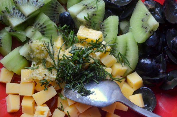 Подготовленные ингредиенты для фруктового салата с сыром и металлическая ложка