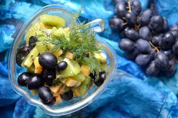 Салат из киви и винограда с сыром и укропом в красивом порционном салатнике на столе с гроздью винограда
