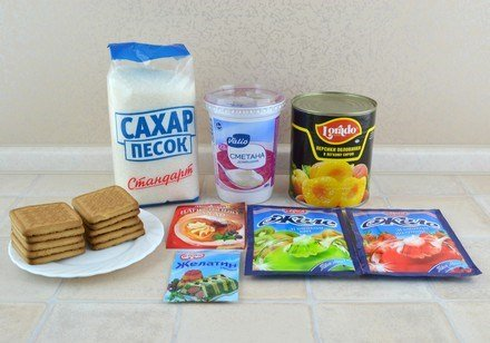 Продукты для приготовления торта «Битое стекло» с печеньем и консервированными персиками на столе
