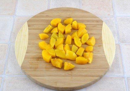Нарезанные маленькими кусочками консервированные персики на круглой разделочной доске