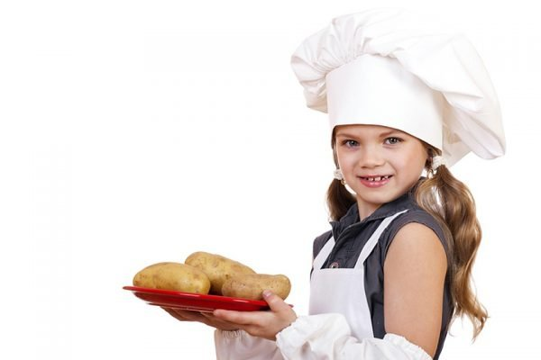 Девочка с вареным картофелем на тарелке