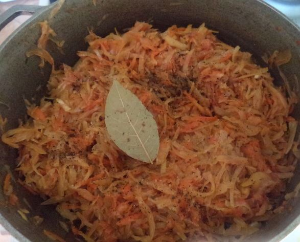 Тушёная капуста в казане с лавровым листом и чёрным молотым перцем