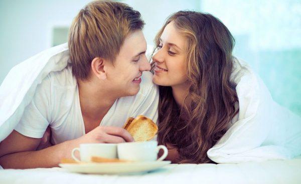 Женщина с мужчиной едят в постели