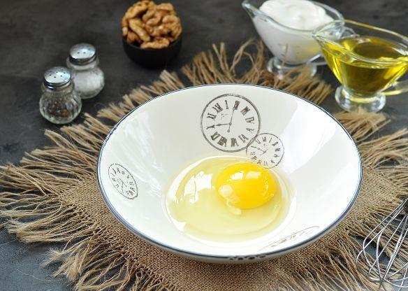 Содержимое сырого куриного яйца в глубокой тарелке на столе