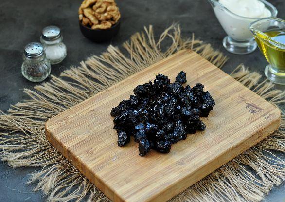 Нарезанный небольшими кусочками произвольной формы чернослив на деревянной разделочной доске