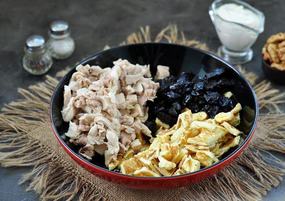 Нарезанные кусочками яичные блинчики, отварное куриное мясо и чернослив в большой миске на столе