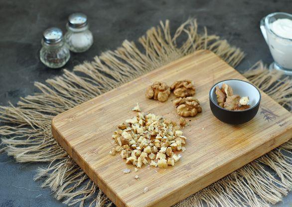 Половинки ядер и рубленые грецкие орехи на деревянной разделочной доске