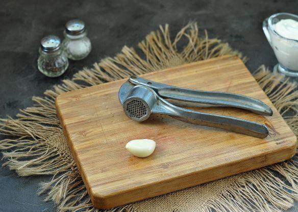 Очищенный от шелухи зубчик чеснока и пресс на деревянной разделочной доске