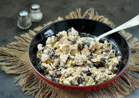 Салат с курицей, черносливом и яичными блинчиками в миске с ложкой на столе