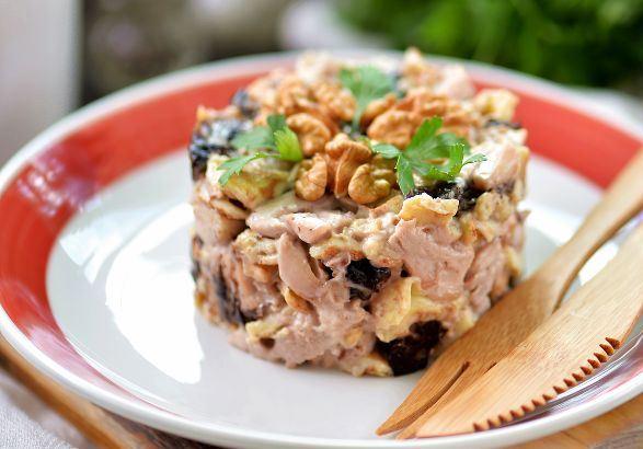 Выложенный с помощью формовочного кольца салат с курицей, черносливом и куриными блинчиками на белой тарелке с красным ободом и деревянными столовыми приборами