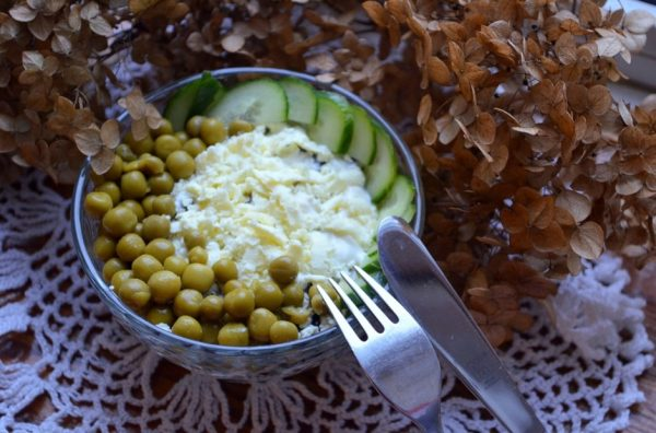 Салат с курицей, черносливом и консервированным горошком в маленьком салатнике с металлическими столовыми приборами