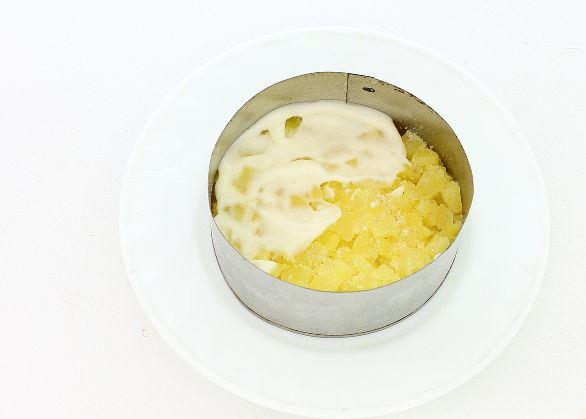 Слой отварного картофеля с майонезом в металлическом формовочном кольце на тарелке