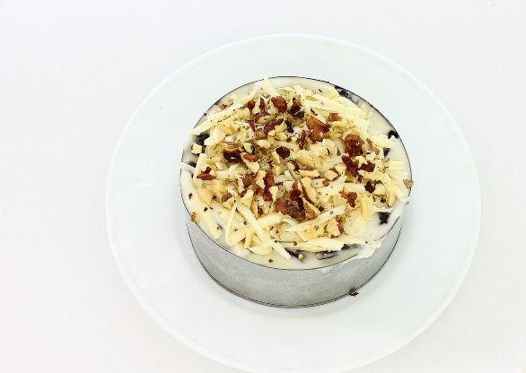 Украшенный тёртым твёрдым сыром и рублеными ядрами грецких орехов салат в формовочном кольце на тарелке