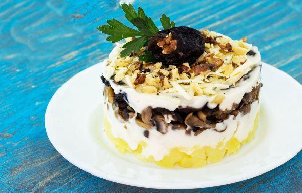Порция салата с курицей, черносливом и картофелем на белой тарелке
