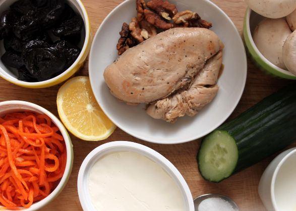 Продукты для приготовления салата с черносливом, курицей и корейской морковью на столе