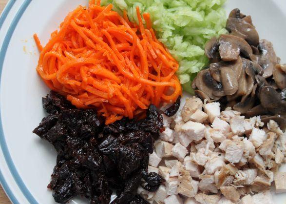 Подготовленные продукты для салата с курицей, черносливом и корейской морковью на большой тарелке