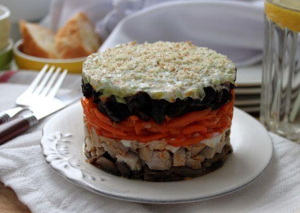 Слоёный салат с курицей, черносливом и морковью по-корейски на сервированном столе