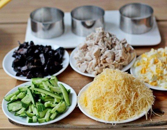 Продукты для приготовления салата с курицей, черносливом, рисом и огурцами на столе