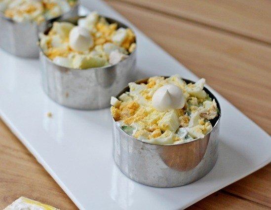 Заготовки салата с курицей и другими ингредиентами в формовочных кольцах на прямоугольной белой тарелке