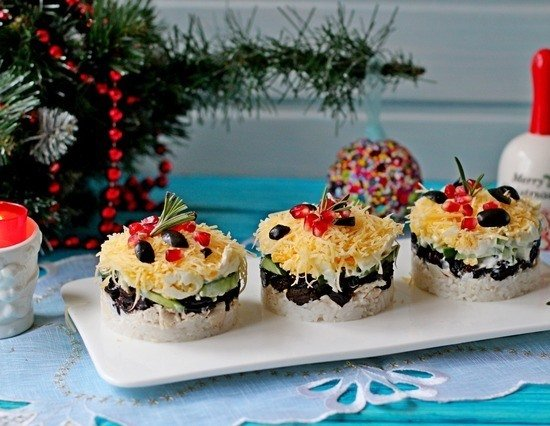 Готовый салат с курицей и черносливом, выложенный порциями на прямоугольную тарелку и рождественский декор
