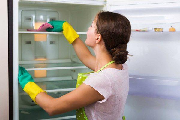 Девушка моет холодильник