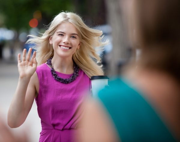 девушка машет рукой