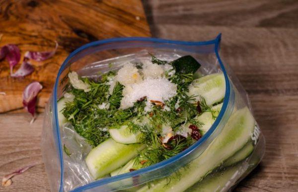 Кусочки свежих огурцов со специями, зеленью, сахаром и солью в пластиковом пакете на столе