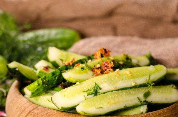 Малосольные огурцы с зеленью и острым перцем в деревянной ёмкости на столе