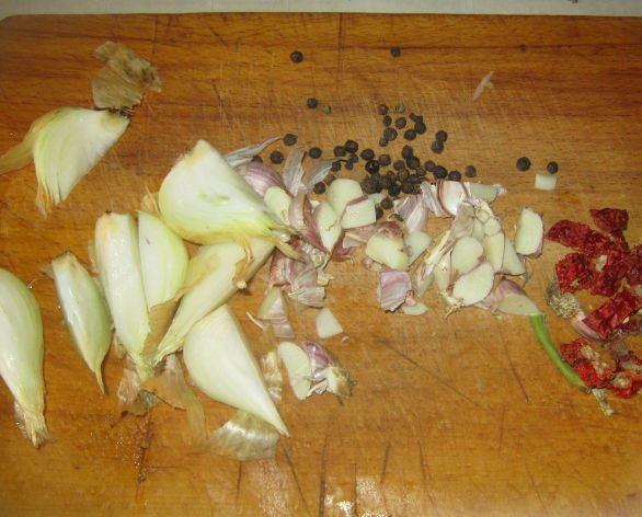 Измельчённый репчатый лук, чеснок, сухой сотрый перец и горошины чёрного перца на деревянной разделочной доске