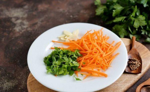 Рубленая свежая зелень, тёртая морковь и измельчённый чеснок на белой тарелке