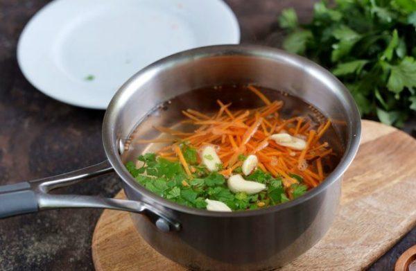 Тёртая морковь, измельчённая зелень и кусочки чеснока в кастрюле с маринадом