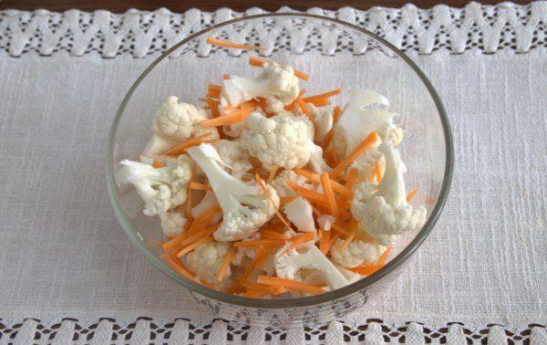 Кусочки сырой цветной капусты с морковью и чесноком в глубокой стеклянной миске