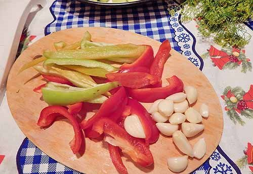 Зубчики чеснока и нарезанный полосками разноцветный болгарский перец на деревянной разделочной доске