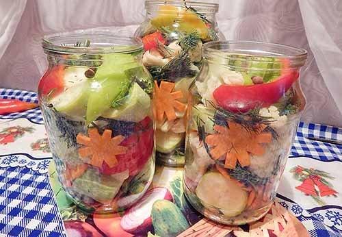 Стеклянные банки с кусочками овощей на столе с клетчатой скатертью