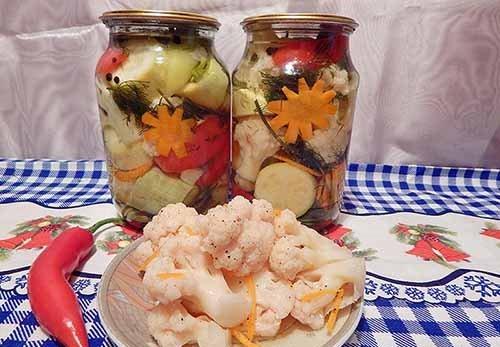 Цветная капуста с кабачками по-корейски в стеклянных банках под крышками и в небольшой тарелке на столе со стручком острого перца