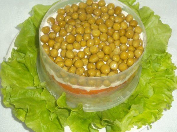 Слой консервированного зелёного горошка в формовочном кольце с другими ингредиентами слоёного салата