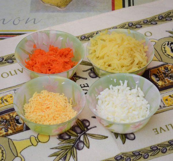 Тёртые отварные белки и желтки, картофель и морковь в разных ёмкостях на столе