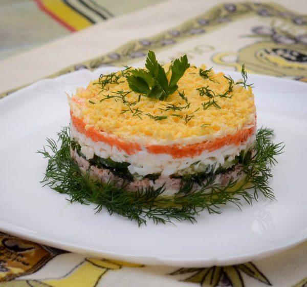 Слоёный салат из печени трески и свежего огурца на большой белой тарелке
