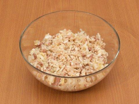 Салат из печени трески с отварным рисом без заправки в стеклянной ёмкости на деревянной поверхности